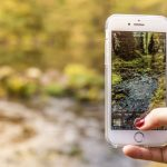 A person holding a phone taking photos of a pond in a forest
